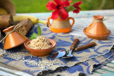 ゆで大麦穀物。タジンで提供しています。生大麦穀物、全粒パンとバック グラウンドでスプーン