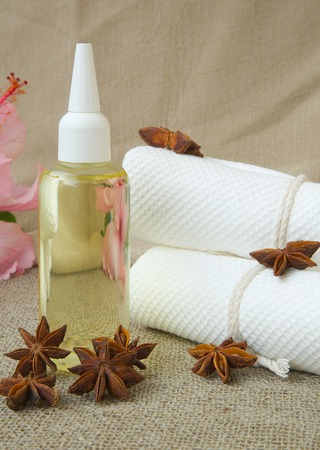 carminative: Star anise hair oil. Star anise fruits in the background. Stock Photo