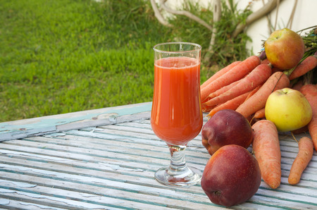 carotenoid: A glass of fresh apple carrot juice on a wooden surface. Fresh carrots and apples in the background.Copy space