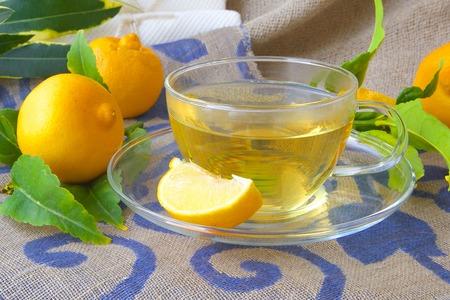 relaxant: A glass cup of  bergamot tea. Fresh bergamot fruits and bergamot tree twigs in the background. Stock Photo