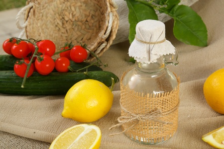 sport fitness: A glass bottle of lemon vinegar. Fresh lemons and vegetables in the background