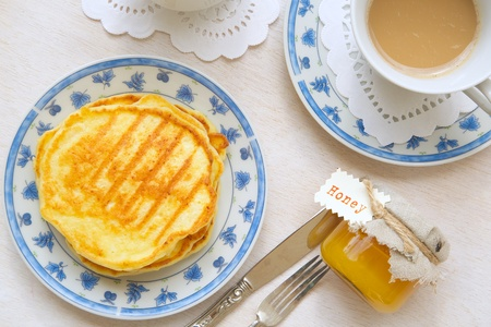 ricotta cheese: Winter breakfast: cup of cappuccino, honey with ricotta cheese pancakes. Background Stock Photo