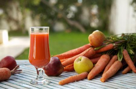 木製の表面の新鮮なリンゴにんじんジュースのガラス。新鮮なニンジンとバック グラウンドでリンゴ。コピー スペース