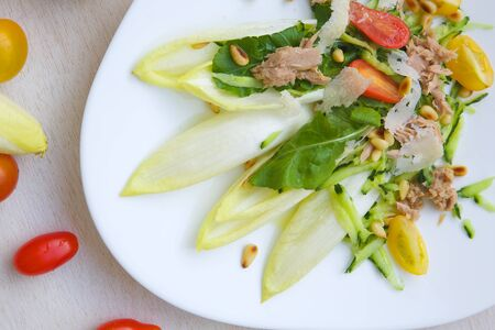 endive: Vitamin winter salad: endive,rucola,tuna,cedar wood nuts,cherry tomatoes,parmesan cheese,cucumber. Background