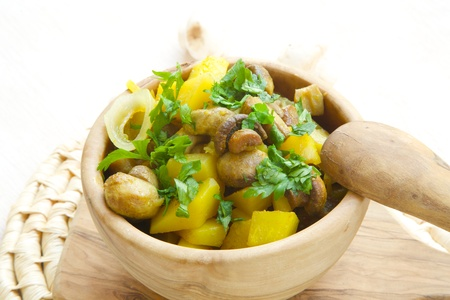 curcumin: Light lunch- baked potatoes with mushrooms,onion,curcuma and fresh leaves of parsley in a olive wood dish. Mushrooms in the background.