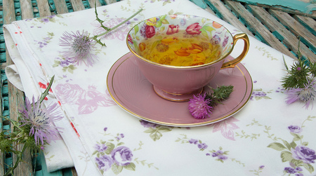 A cup of milk thistle tea on a table cloth. Milk thistle blossoms are in the background