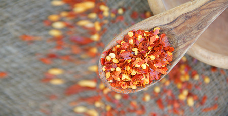 close p: Dried crushed red hot chili pepper in a wooden made spoon Stock Photo