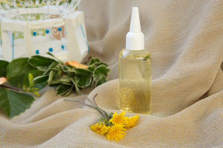 microbial: Dandelion hair oil. Dandelion blossoms in the background