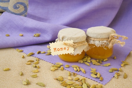 traditional remedy: Glasses of honey and cardamom in the background Stock Photo