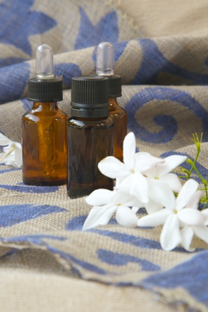 benzoic: A dropper bottle of jasmine essential oil. Jasmine blossoms in the background