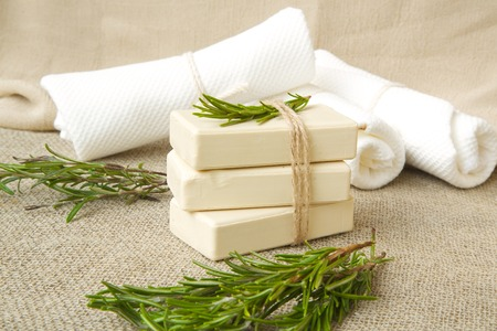 relieving pain: Soap bars with rosemary essential oil.Rosemary twigs in the background Stock Photo