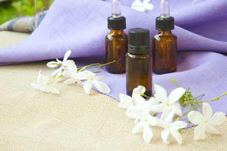 A dropper bottle of jasmine essential oil. Jasmine blossoms in the background
