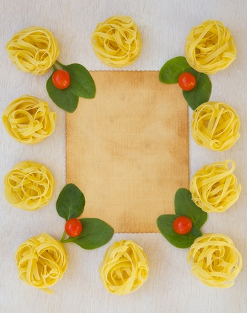text free space: Pasta ingredients background: fresh leaves of spinach,cherry tomatoes,raw tagliatelle. Free space for a text