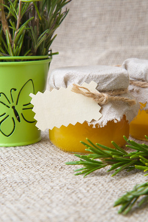 text free space: Glasses of rosemary honey. Rosemary twigs in the background. Closeup. Free space for a text. Stock Photo