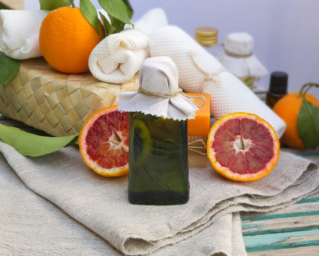 limonene: A glass bottle of blood orange oil. Spa products in the background. Stock Photo