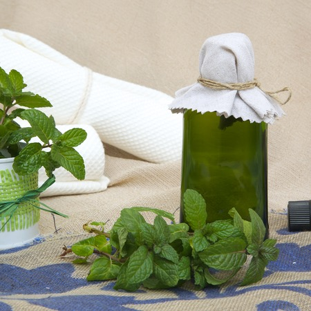 spasms: A glass bottle of peppermint oil. Peppermint leaves in the background