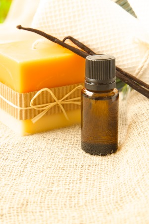 A dropper bottle of vanilla essential oil. Vanilla sticks and a candle in the background.