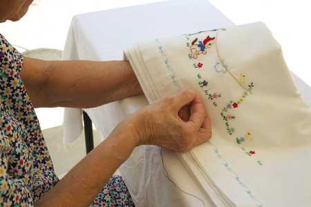 70 80 years: An old woman between 70 and 80 years old is embroidering on a white linen blanket at fine weatheron the terrace. Body parts