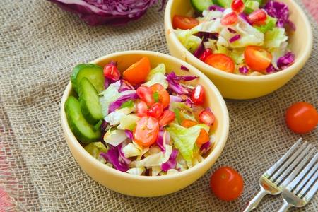 Uroczysta witaminy sałatki: ogórki, zielona cebula, pomidory koktajlowe, zielone liście sałaty, fioletowy kapusta, ziarna granatu. Widły na szarym wory.