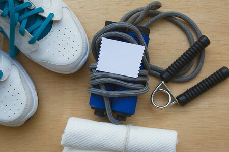 gripper: Free space for a text on a piece of pape. Sport items background: snickers,jumping rope,white towel, hand gripper.