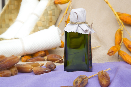 muscle gain: A glass bottle of dates seeds oil. Dates in the background.