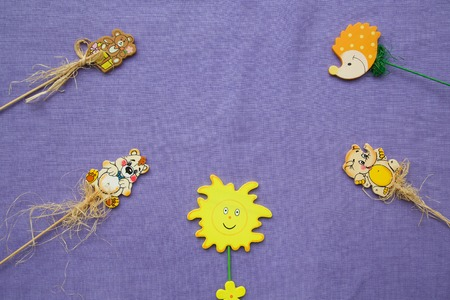not painted: Violet fabric with different wooden made figures: bear,sun,hedgehog,birthday present,elephant. Free space for a text.