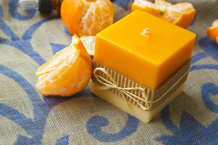 limonene: A candle with mandarin fragrance. Fresh mandarins in the background