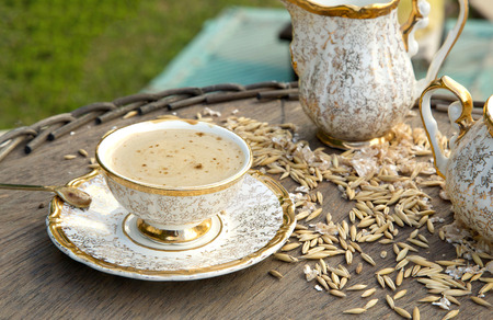 substitute: Healthy breakfast drink in an old porcelain cup: coffee substitute barley drink.Barley grains and flakes in the background.