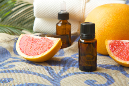 A dropper bottle of grapefruit essential oil. Grapefruits in the background. Stock Photo