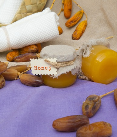 muscle gain: Dates honey in small glasses. Dates in the background