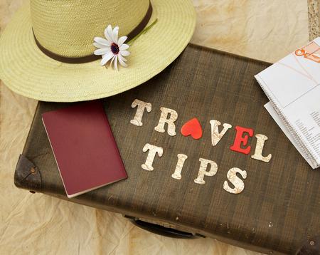 旅行: 夏の旅行帽子、花、古いスーツケース、茶色のパスポート、地図と木の手紙:「旅行のヒント」