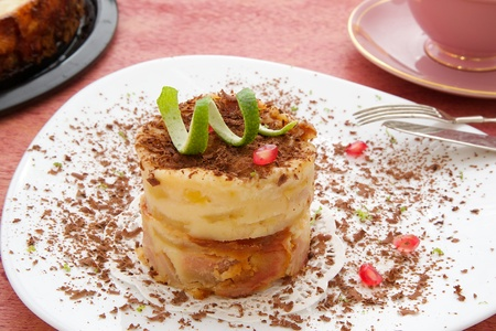 kin: A piece of  cheese cake with chocolate chips,lemon skin and pomegranate grains on a white plate. Cake is in the mould and a cup of tea on a red wooden surface. Closeup