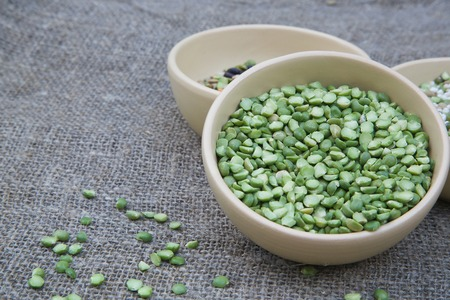 free dish: Dried green peas in a brown clay dish. Free space for a text