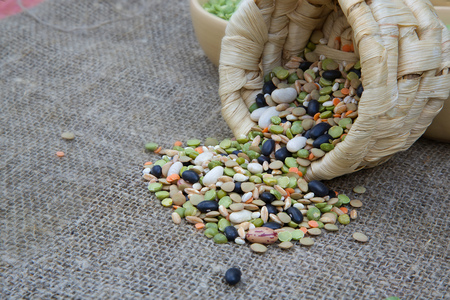pearl barley: An assortment of dried legumes and cereals: wheat grains, green peas, French beans,pearl barley, orange lentils on a grey sackcloth