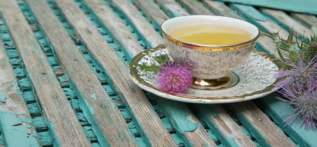 テーブル クロスにシスル ミルクティーのカップ。ミルク シスルの花は、バック グラウンドでです。テキスト用の空き容量