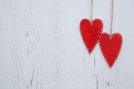 pared madera: Dos corazones de madera rojas que cuelgan en una pared de madera vieja