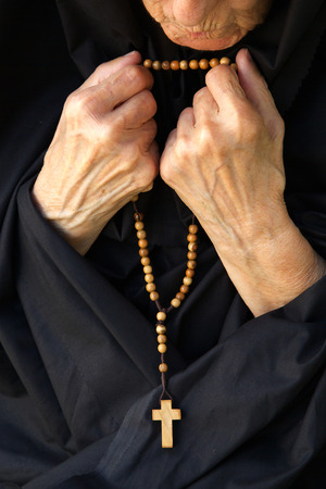 front view: A senior woman  in black dress is praying. Front view