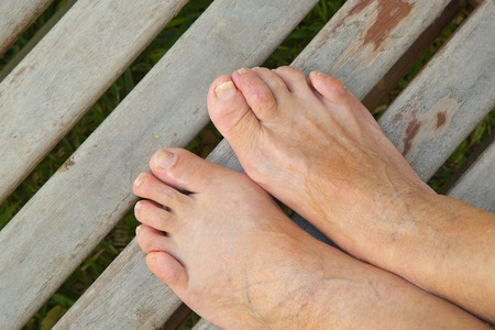 The feet of an old woman on an old wooden surface.