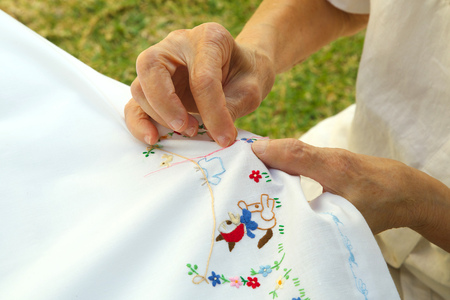80 years: An old woman between 70 and 80 years old is embroidering on the white linen blanket at fine weather in the garden. Body parts Stock Photo
