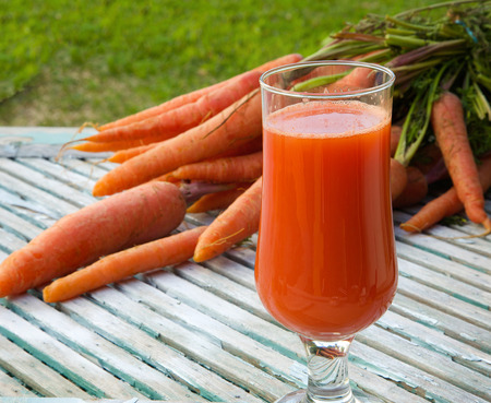 carotenoid: A glass of fresh carrot juice on a wooden surface. Fresh carrots in the background