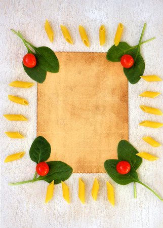 text free space: Pasta ingredients background: fresh leaves of spinach,cherry tomatoes,raw penne regate. Free space for a text Stock Photo