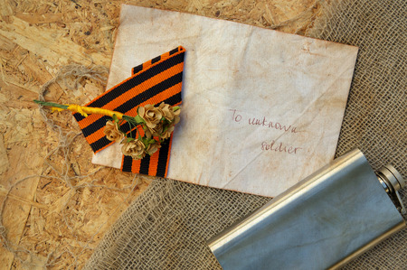 hip flask: Saint George ribbon,hip flask,paper roses,letter to unknown soldier and free space for a text. Background.Close up Stock Photo
