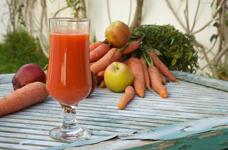 carotenoid: A glass of fresh apple carrot juice on a wooden surface. Fresh carrots and apples in the background.Copy space.Close up