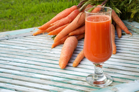 carotenoid: A glass of fresh carrot juice on a wooden surface. Fresh carrots in the background. Free space for a text Stock Photo