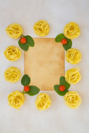 free space: Pasta ingredients background: fresh leaves of spinach,cherry tomatoes,raw tagliatelle. Free space for a text