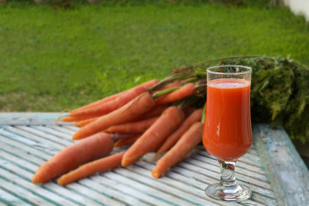 carotenoid: A glass of fresh carrot juice on a wooden surface. Fresh carrots in the background. Free space for a text Foto de archivo
