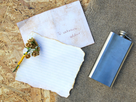 hip flask: A letter to unknown soldier,paper roses,hip flask,free space for a text. Background