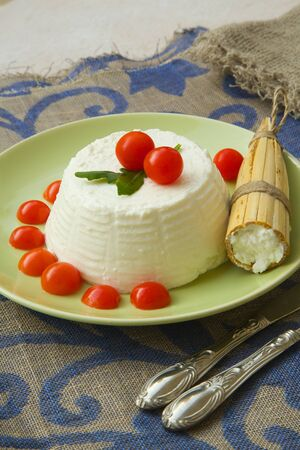 ricotta cheese: Ricotta cheese with cherry tomatoes and rucola and a Sicilian traditional mould for making ricotta - cavagne.