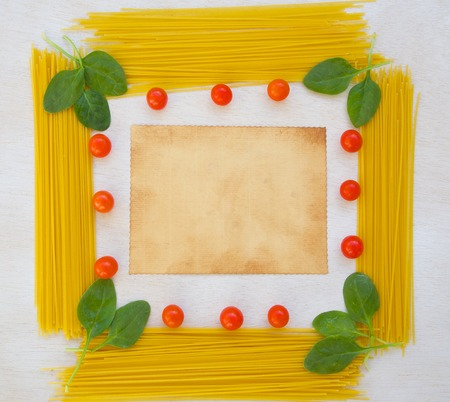 text free space: Pasta ingredients background: fresh leaves of spinach,cherry tomatoes,spaghetti. Free space for a text Stock Photo