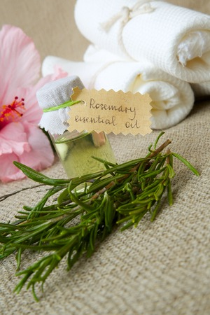relieving pain: A bottle of rosemary essential oil on a sackcloth. Rosemary twigs and hibiscus flowers in the background